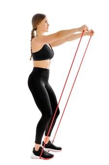 Kobieta lekkoatletka trenująca z opaską siłową, wykonująca ćwiczenia unoszenia czołowego w celu wzmocnienia jej mięśni
