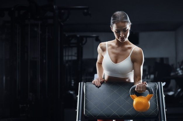 Kobieta lekkoatletycznego fitness na treningu w siłowni pompowania mięśni z kettlebell. tło koncepcji fitness i sportu