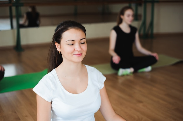 Kobieta lekkoatletycznego robi ćwiczenia relaksacyjne w klasie siłowni.