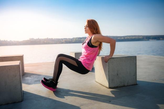 Kobieta lekkoatletycznego robi ćwiczenia w kucki w słonecznym parku, w pobliżu jeziora