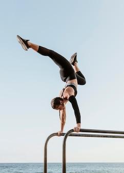 Kobieta lekkoatletycznego robi trening fitness przy plaży