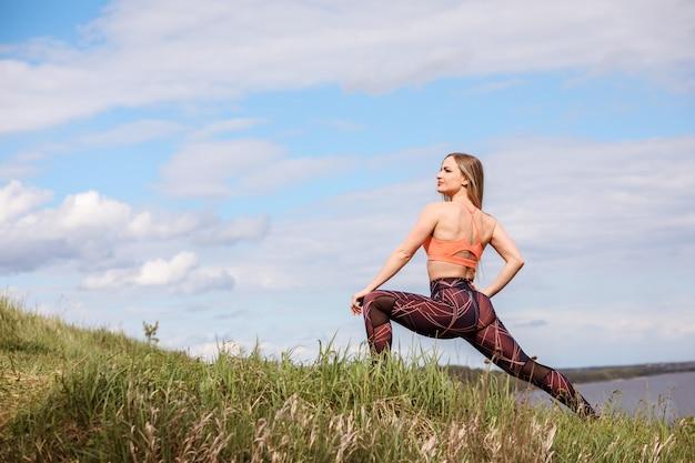 Kobieta lekkoatletycznego robi wypad, trening na świeżym powietrzu z natury.