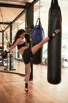 Kobieta lekkoatletycznego szkolenia ciężko kopiąc worek treningowy