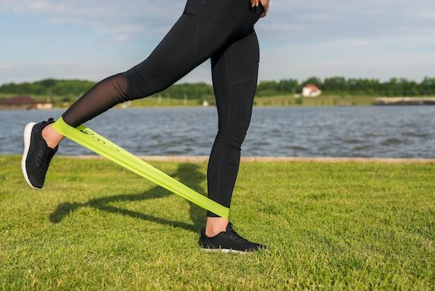 Kobieta lekkoatletycznego treningu z zespołem oporu na zewnątrz. dziewczynka fitness robi ćwiczenia dla pośladków w parku