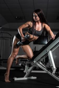 Kobieta lekkoatletycznego trenuje z hantlami, pompując jego biceps