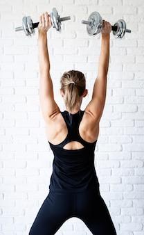 Kobieta lekkoatletycznego w czarnej odzieży sportowej, pokazując jej mięśnie pleców i ramion, trening z hantlami