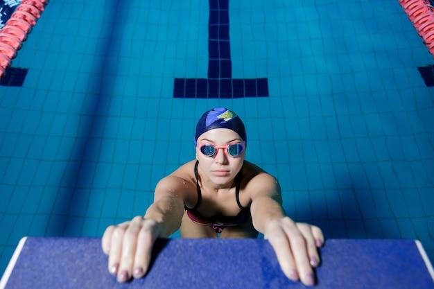 Kobieta lekkoatletycznego w kapelusz i okulary gotowe do rozpoczęcia wyścigu pływania w basenie