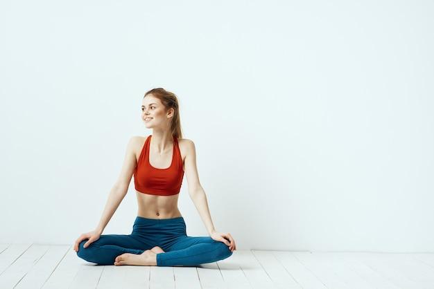 Kobieta lekkoatletycznego w pozie na tle jasnym tle wykonywania gimnastyki ćwiczenia.