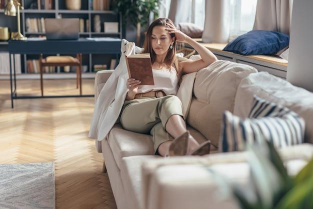 Kobieta, leżąc na kanapie i czytając książkę w domu.