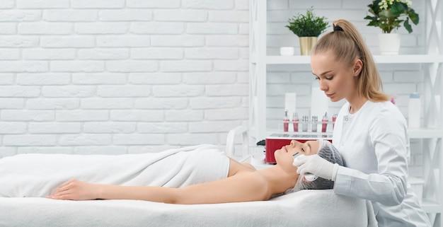Kobieta leżąc na kanapie na zabieg na twarz w gabinecie kosmetycznym