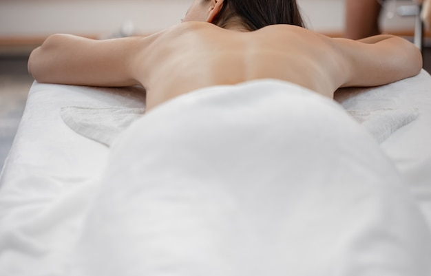 Kobieta leżąc na kanapie w salonie kosmetycznym na relaksujący masaż.