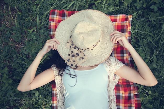 Kobieta, leżąc na kapeluszu trawa na twarzy