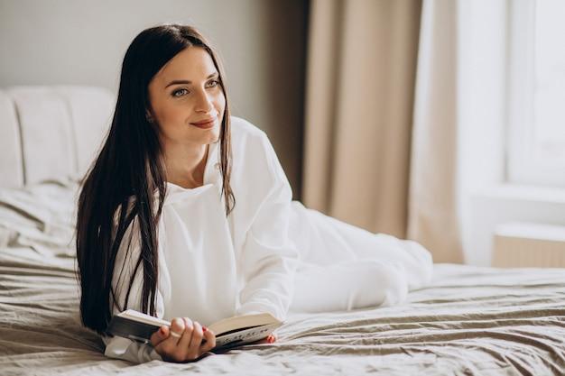 Kobieta, leżąc na łóżku i czytając książkę