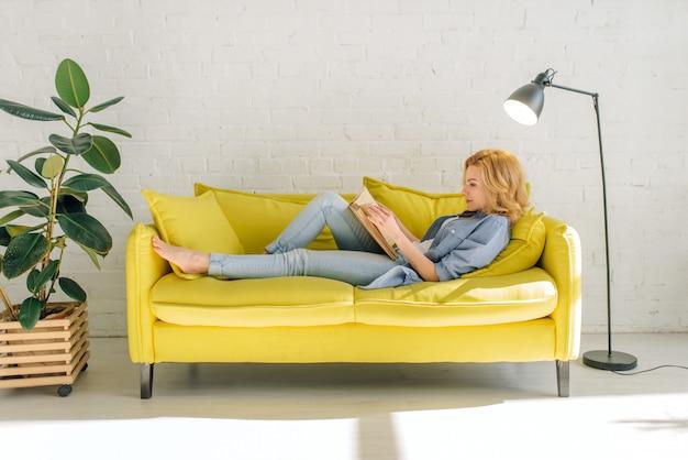 Kobieta, leżąc na przytulnej żółtej kanapie i czytając książkę