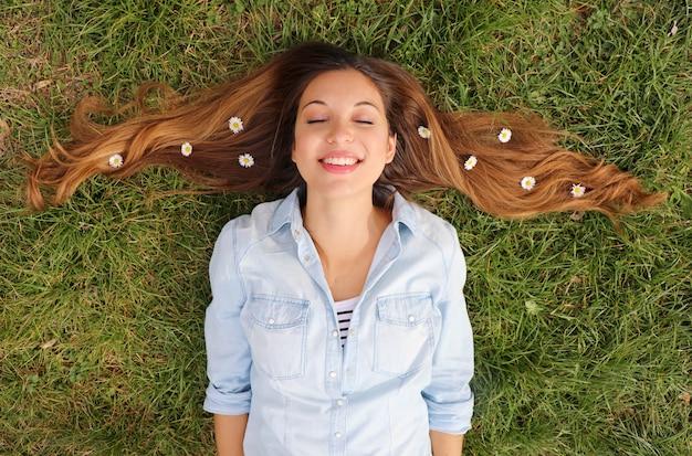 Kobieta, leżąc na trawie ze stokrotkami we włosach
