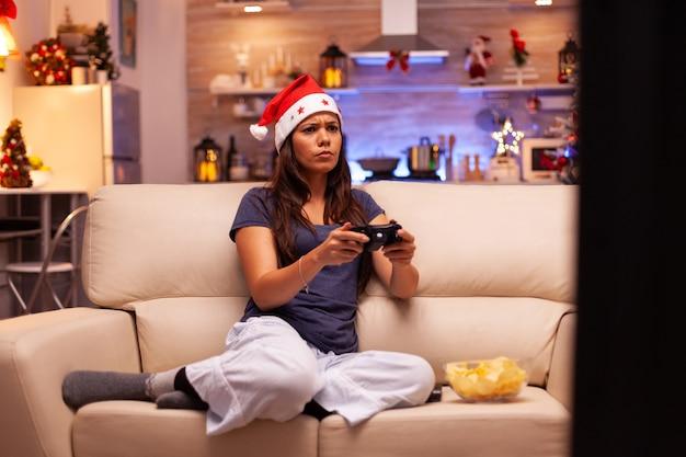 Kobieta leżąca na kanapie grająca w gry wideo online za pomocą joysticka do gier