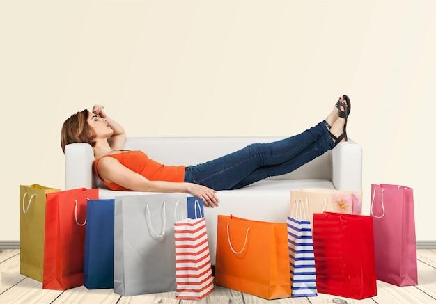 Kobieta leżąca na kanapie za rzędem toreb zmęczona po zakupach