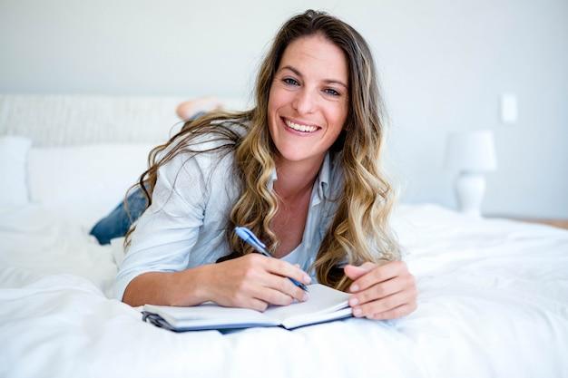 Kobieta leżąca na łóżku, uśmiechnięta i pisząca w książce piórem
