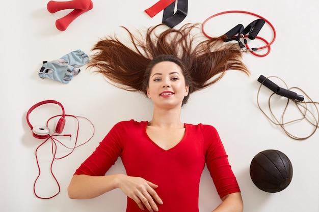 Kobieta leżąca na podłodze po treningu z hantlami, skakanka, rękawice fitness, ekspander, gumka, wygląda na szczęśliwą i zdrową, kobieta nosi czerwoną odzież, sportowa dziewczyna na białej powierzchni.