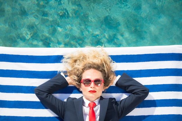 Kobieta leżąca na ręczniku w paski w pobliżu basenu letnie wakacje i koncepcja podróży wolności