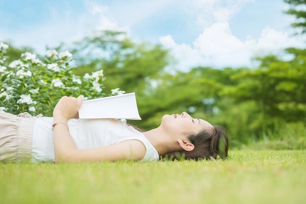 Kobieta leżąca na trawie do spania po zmęczeniu czytaniem książki
