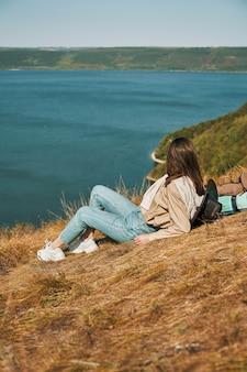 Kobieta leżąca na zielonym wzgórzu podczas wędrówki po okolicy bakota