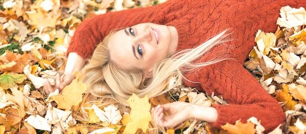 Kobieta leżąca na żółtych liściach