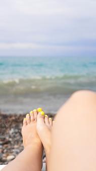 Kobieta leżąca w pobliżu wody. nogi kobiety w pobliżu błękitnego morza - pionowe zdjęcie