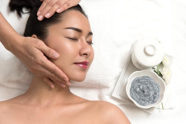 Kobieta leżącego i przygotowanie twarzy lub głowy masażu w spa