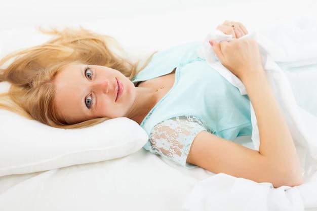 Kobieta leży na białym arkuszu w łóżku w domu