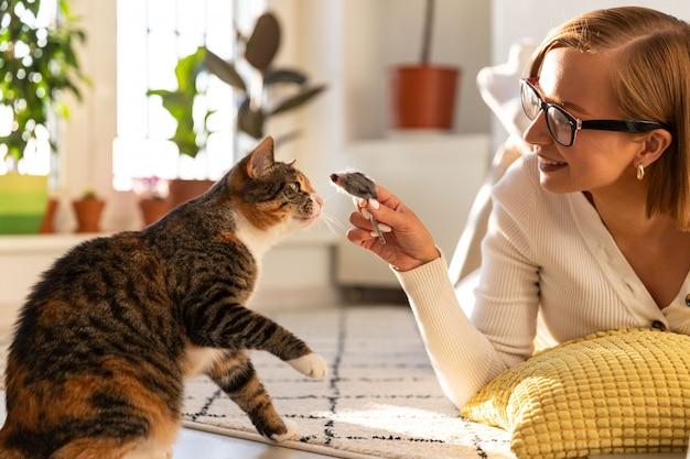 Kobieta leży na dywanie w salonie, bawi się kotem i zabawkową myszką