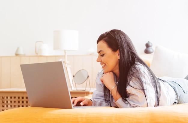Kobieta leży na kanapie w domu, koncentrując się na pracy na laptopie