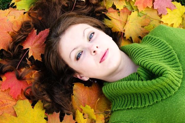 Kobieta leży na liściach klonu. zamknij twarz.