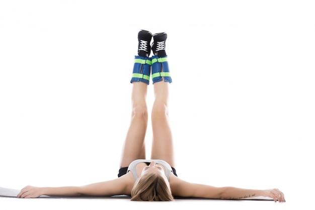 Kobieta leży na podłodze z podniesionymi nogami