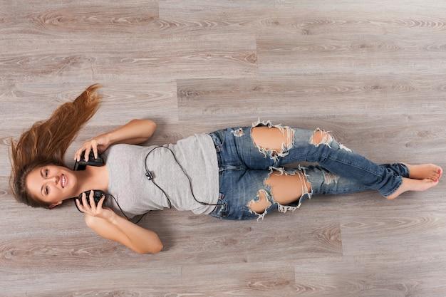 Kobieta leży na podłodze ze słuchawkami