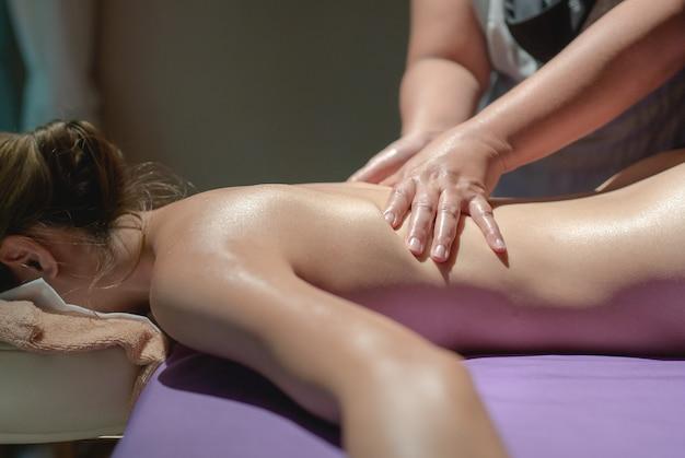 Kobieta leży na stole do masażu. relaksujący masaż pleców w spa, leczniczy zabieg na ciało.