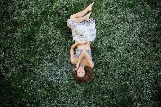 Kobieta leży na trawie patrząc z góry
