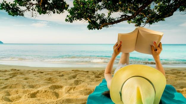Kobieta leży na zielonym ręczniku, który stawia na piaszczystej plaży pod drzewem i czyta książkę.