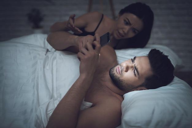 Kobieta leży w ciemnym pokoju w łóżku z facetem.