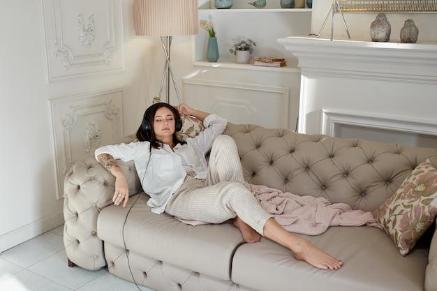 Kobieta leży w domu na kanapie z włączonymi słuchawkami i słucha muzyki