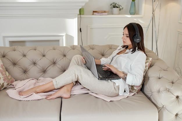 Kobieta leży w domu na kanapie ze słuchawkami i słucha muzyki. dzień wolny w domu, relaks i odpoczynek