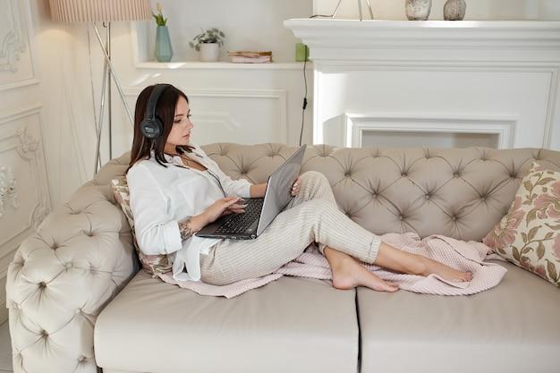 Kobieta leży w domu na kanapie ze słuchawkami i słucha muzyki