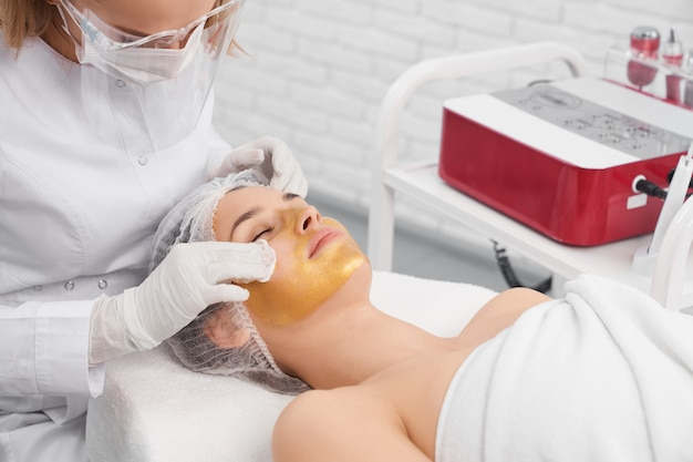 Kobieta leży w kosmetyczce i robi zabieg na twarz