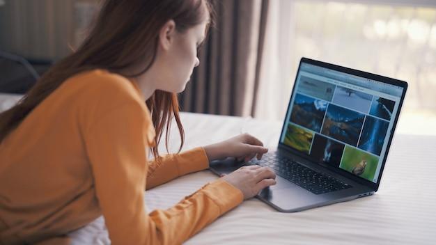Kobieta leży w łóżku przed niezależną komunikacją laptopa