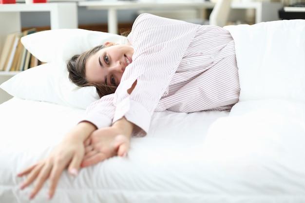 Kobieta leży w łóżku w koszuli i uśmiecha się.