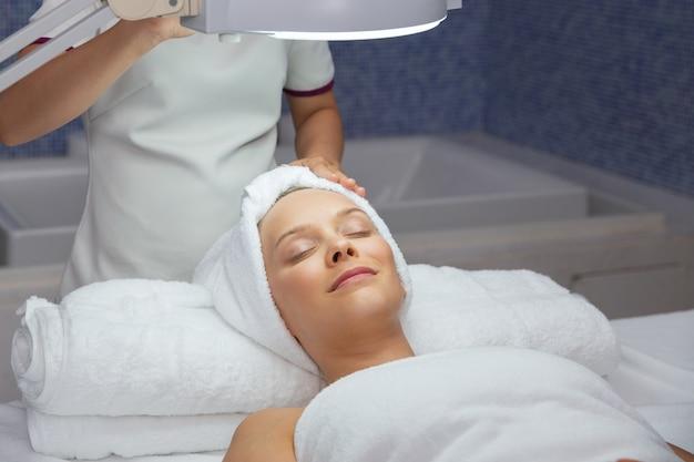 Kobieta leży w pokoju masaż twarzy w górę