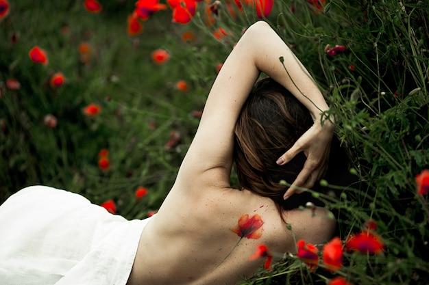Kobieta leży z gołymi plecami z tatuażem zakrytym białą koszulą wśród kwiatów maku