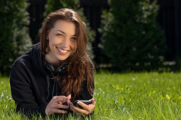 Kobieta leży z telefonem na trawie w ogrodzie obok domu i szeroko się uśmiecha. relaks na koncepcji trawnika. rekreacja na świeżym powietrzu. wakacje we wsi. ciepły, słoneczny letni dzień.