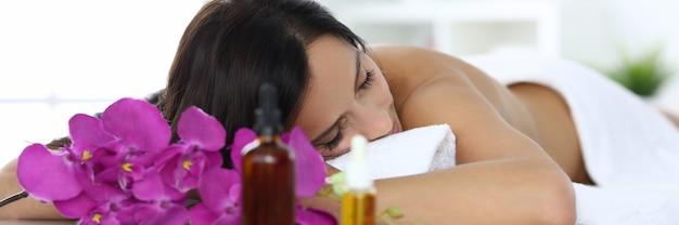 Kobieta leży z zamkniętymi oczami na stole do masażu w centrum spa. relaksujący koncepcja masażu odprężającego