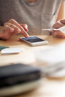 Kobieta liczenia pieniędzy na swoim telefonie